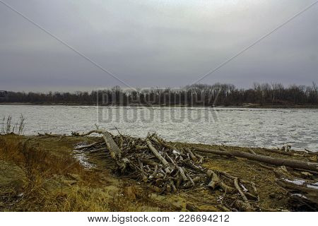 Icy Missouri River With Pile Of Driftwood On The River Bank In Saint Charles Missouri