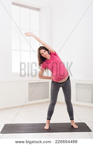 Pregnant Woman Warmup Stretching Training At Home. Expectant Female Makes Aerobics Exercise, Healthy