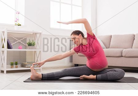 Pregnant Woman Stretching Training At Home, Copy Space. Expectant Female Makes Warmup Aerobics Exerc