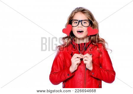 Portrait of a cute pre-teen girl holding two little hearts. Isolated over white. First love. Valentine's Day.