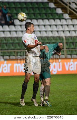 KAPOSVAR, HUNGARY - JULY 30: Zoltan Liptak (in white 5) in action at a Hungarian National Championship soccer game - Kaposvar (green) vs Videoton (white) on July 30, 2011 in Kaposvar, Hungary.