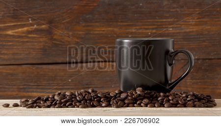 Seeds Of Coffee In A Black Cup On A Wooden Background Close Up