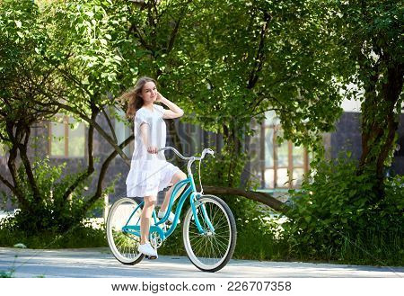 Long Haired Young Woman In A Dress Riding Bicycle In The Bark Copyspace Emotions Freedom Freshness W