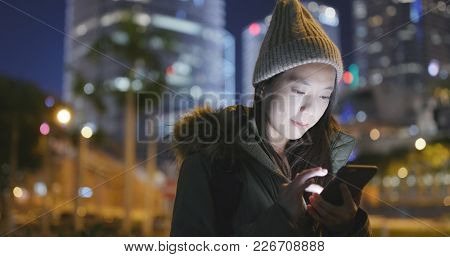 Woman wearing winter jacket and using cellphone at night