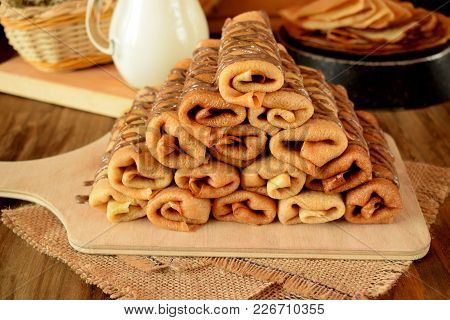 Pile Of Rolled Crepes With Banana Filling On A Wooden Board