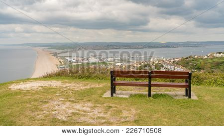 A Bench On The South West Coast Path  With View Towards Fortuneswell And Chesil Beach, Isle Of Portl