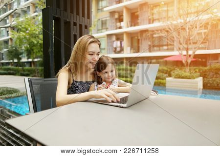 Happy Parent Mother And Daughter Using Laptop On Background Of Swimming Pool During Sunny Day. Conce