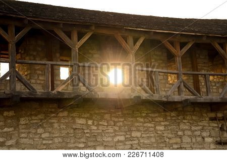 Stone Wall Of An Ancient Castle With A Long Wooden Balcony Through A Window The Sun Shines Brightly