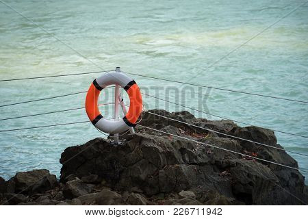 Orange Lifebuoy Hanging On A Column In A Park Near The Lake