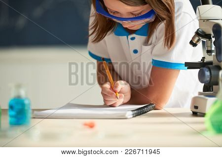 Schoolgirl Writing Chemical Formula In Her Texbook