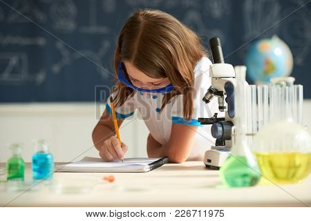 Little Girl In Goggles Writing In Textbook At Chemistry Class