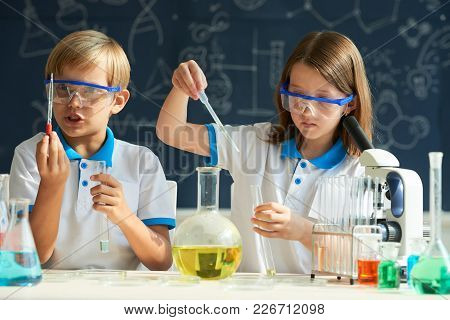 Smart Children Conducting Experiment At Chemistry Class