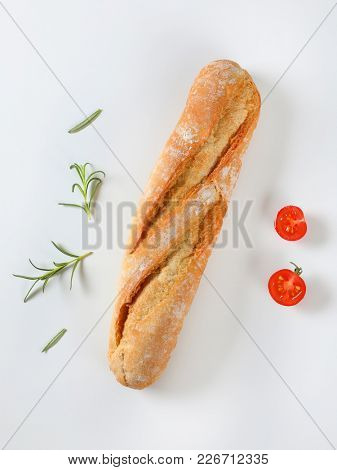 short French baguette, rosemary and cherry tomato on white background