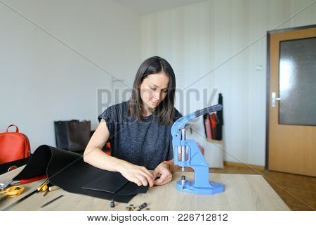 Girl Cutting Piece Of Leather Of Necessary Form For Making Women Bag. Young Woman Interested In Maki