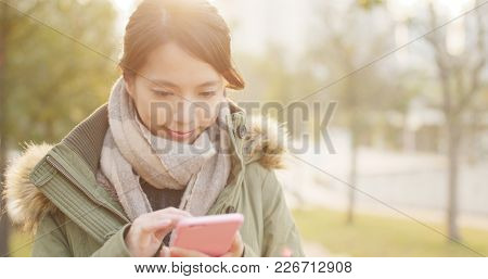 Woman use of mobile phone under sunset time