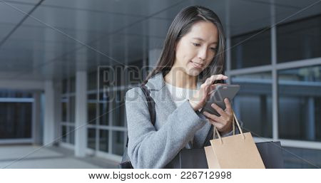 Woman using cellphone and holding paper bag