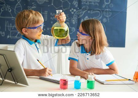 Boy Explaining Properties Of Chemical Liquid To His Classmate