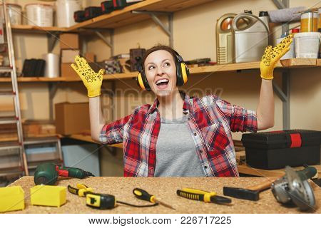 Young Woman In Plaid Shirt, Gray T-shirt, Noise Insulated Headphones, Yellow Gloves Spreading Hands