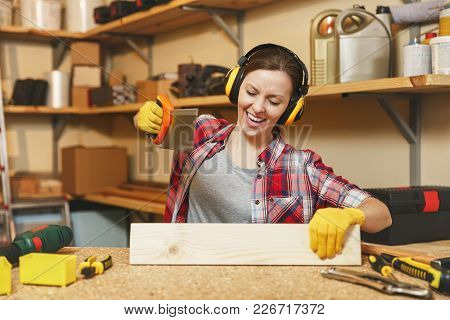 Pretty Caucasian Young Brown-hair Woman In Plaid Shirt, Gray T-shirt, Noise Insulated Headphones, Ye