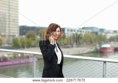 Journalist Talking On Smartphone, Woman In Business Clothes Go To Work. Smiling Middle-aged American