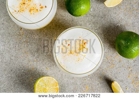 Peruvian, Mexican, Chilean Traditional Drink Pisco Sour Liqueur, With Fresh Lime, On Gray Stone Tabl