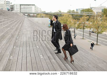 Ceo Man Talking On Smartphone And Secretary Woman Go To Work, Colleagues Americans Climbing Stairs.
