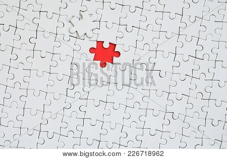 The Texture Of A White Jigsaw Puzzle In An Assembled State With One Missing Element Forming A Red Sp