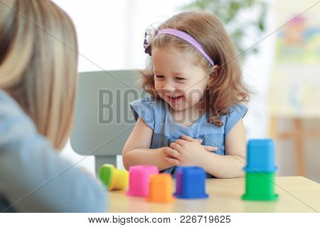 Woman And Kid Playing Colorful Block Toys At Home Or Kindergarten