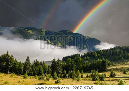 Beautiful Mountain Landscape With Rainbow And Mist.