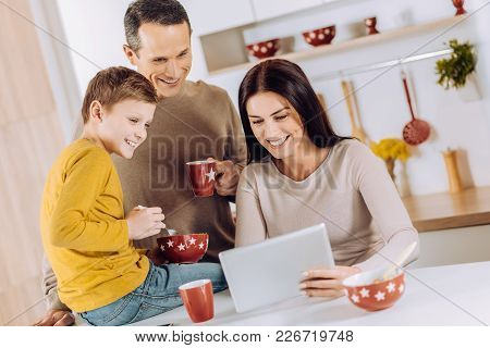 Pleasant Breakfast. Upbeat Young Family Having Breakfast In The Kitchen And Watching A Video On Tabl