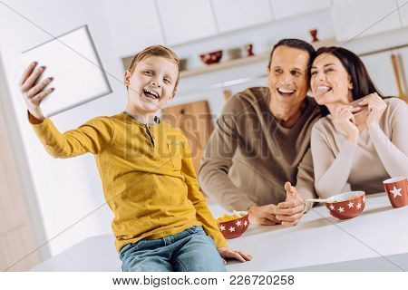 Precious Moment. Joyful Little Boy Sitting On The Kitchen Counter And Taking A Selfie Of Himself And