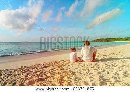 Father And Little Son Looking At Sea On Tropical Beach