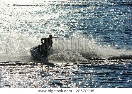 Man on Jet Ski turns fast on the water