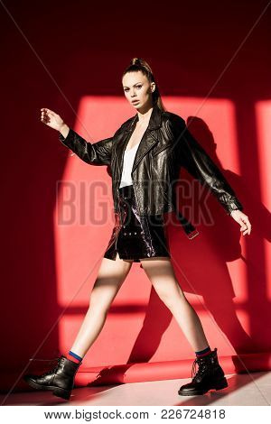 Stylish Girl Posing In Leather Jacket For Fashion Shoot On Red