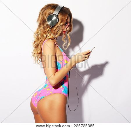 young woman wearing swimmsuit dancing and listening for the musi