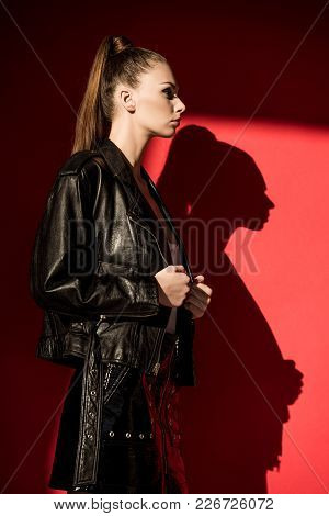 Side View Of Stylish Girl With Ponytail Hairstyle Posing In Black Leather Jacket For Fashion Shoot O
