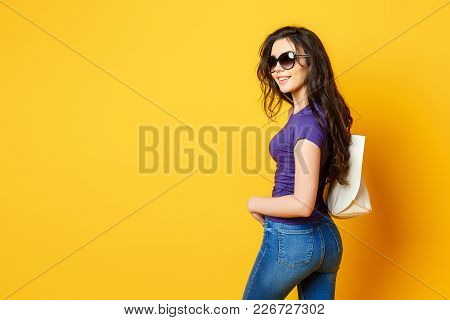 Beautiful Young Woman In Sunglasses, Purple Shirt, Blue Jeans Posing With Bag On The Wonderful Yello