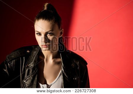 Portrait Of Attractive Young Woman Posing In Black Leather Jacket For Fashion Shoot On Red