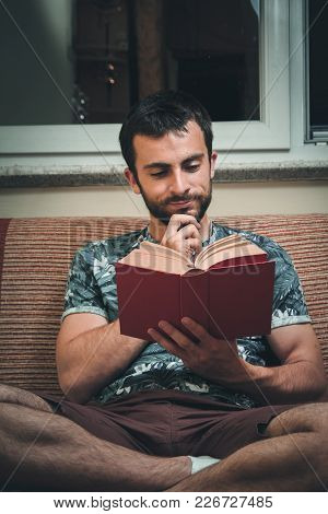 Young Man Enjoying Reading A Book Very Much, Immersed In The Story
