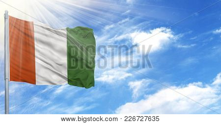 Flag Of Cote D,lvoire On Flagpole Against The Blue Sky.