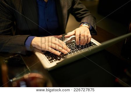 Hands Of Businessman Working On Laptop At Restaurant Table
