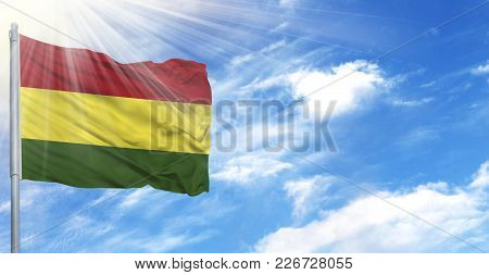 Flag Of Bolivia On Flagpole Against The Blue Sky.