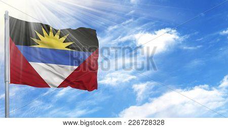 Flag Of Antigua And Barbuda On Flagpole Against The Blue Sky.