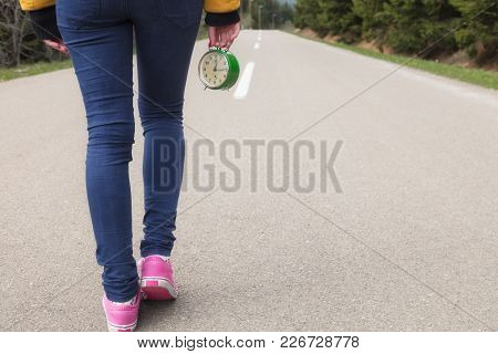 Girl Holding A Vintage Old Clock On A Empty Road.