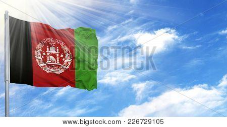 Flag Of Afghanistan On Flagpole Against The Blue Sky.