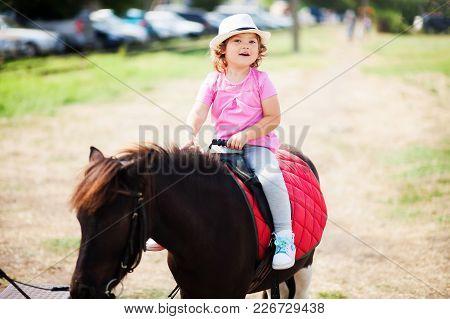 Cute Toddler Girl Riding A Horse.