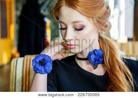 A Girl With A Beautiful Make-up And With Handmade Ornaments In A Cafe