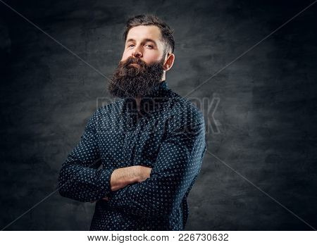 A Stylish Bearded Tattooed Male Dressed In Dark Blue Jacket Over Grey Background.