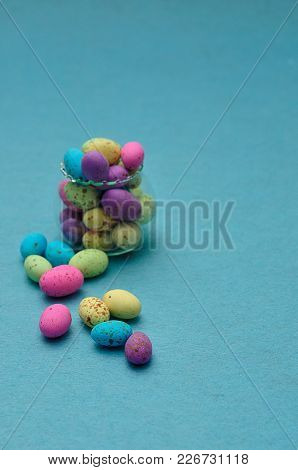 A Small Glass Container Filled With Colorful Speckled Eggs On A Blue Background