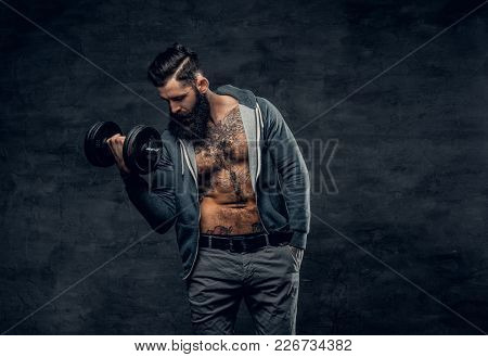Studio Portrait Of Athletic Bearded Male In A Grey Hoodie Holds Dumbbell.